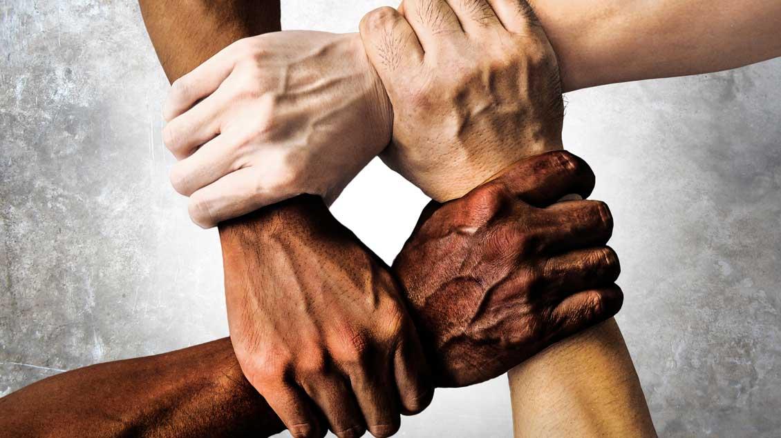 Vier Hände unterschiedlicher Hautfarbe
