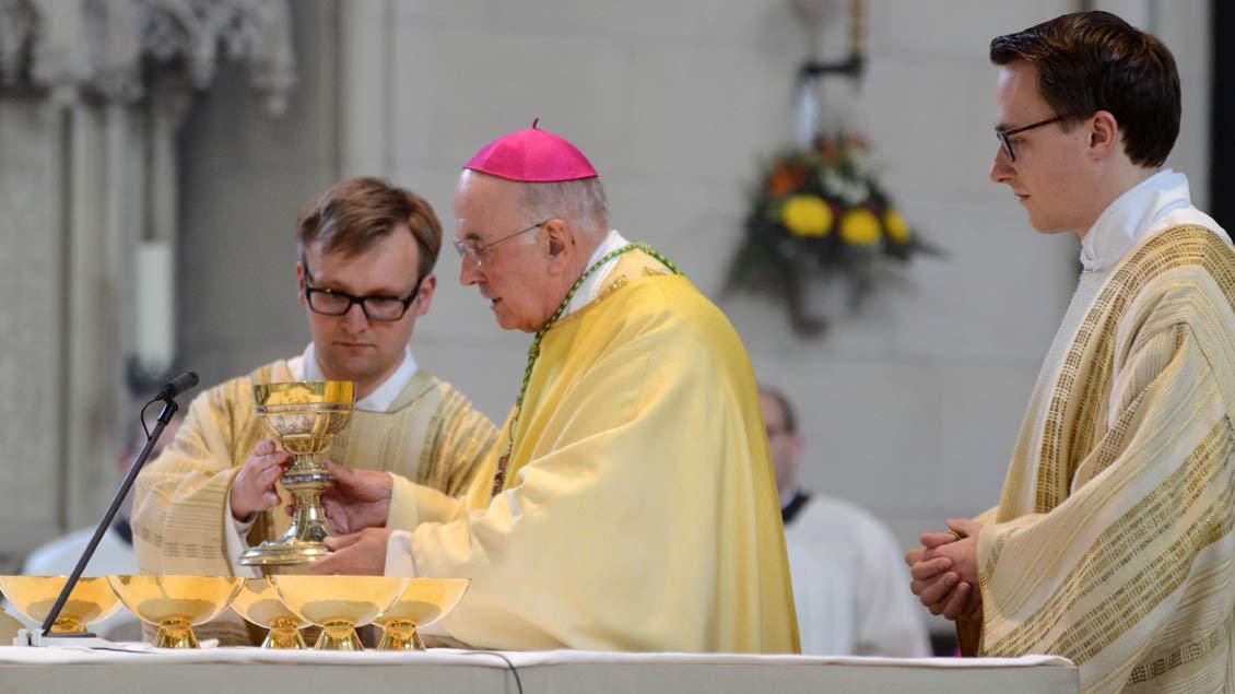 Gabenbereitung: Gemeinsam mit Bischof Genn bereiten Jan Tasler (links) und Fabian Guhr als Diakone bei der Gabenbereitung Brot und Wein vor.