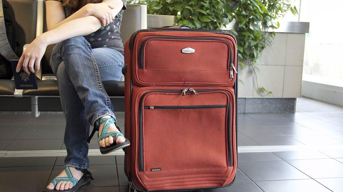 Junge Frau wartet mit ihrem Koffer am Flughafen.