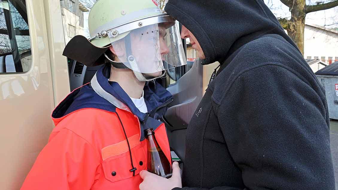Ein Mann in Kapuzenpulli mit einer Bierflasche in der Hand bedroht einen Malteser in Uniform.