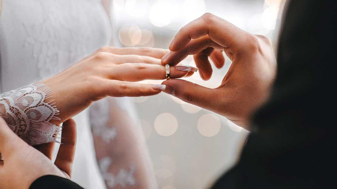 Ein Brautpaar steckt einander die Ringe an.