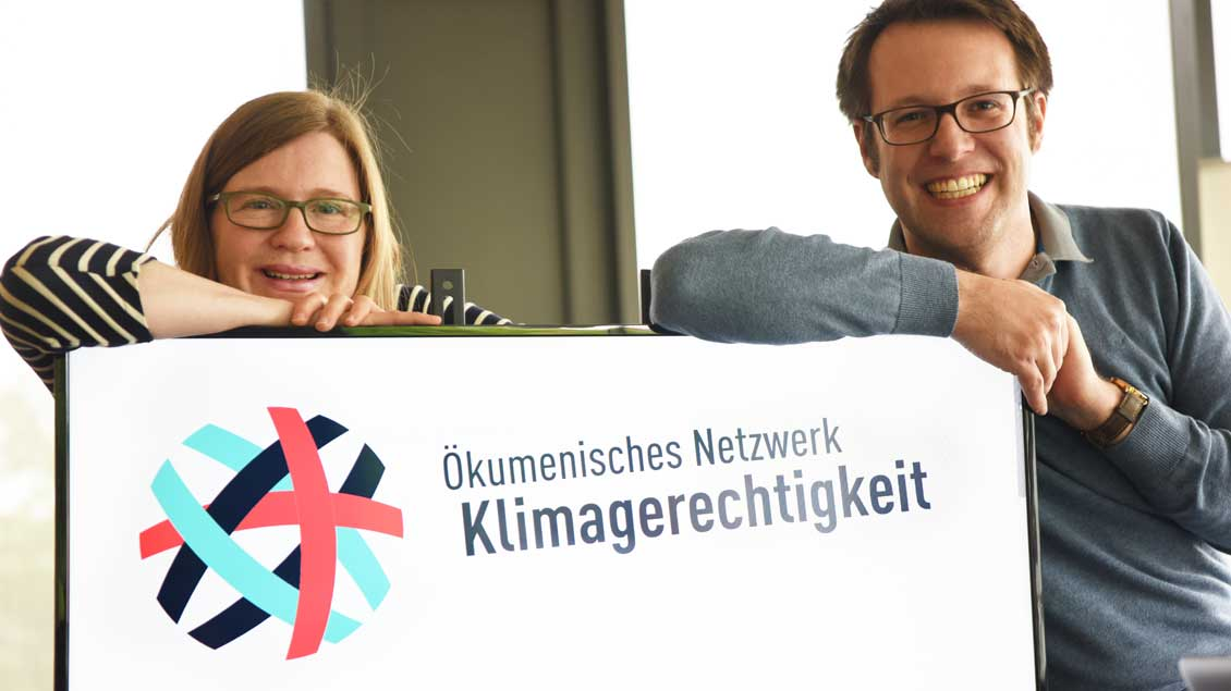 Monika Schell und Chris Böer mit einem Banner des Ökumenischen Netzwerks Klimagerechtigkeit.