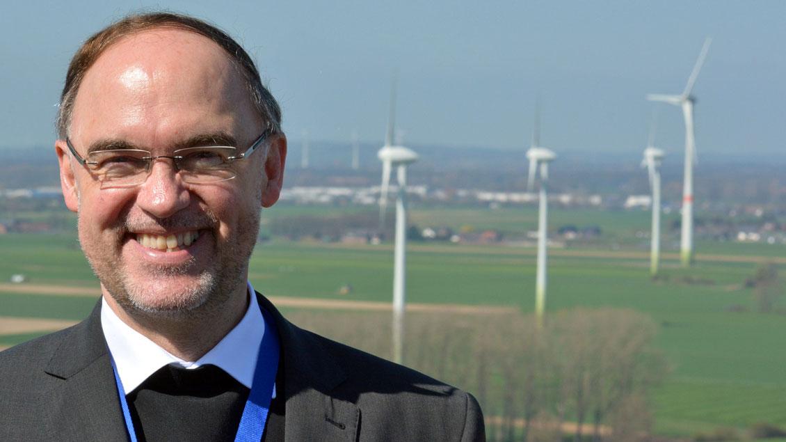 Rolf Lohmann vor Windrädern