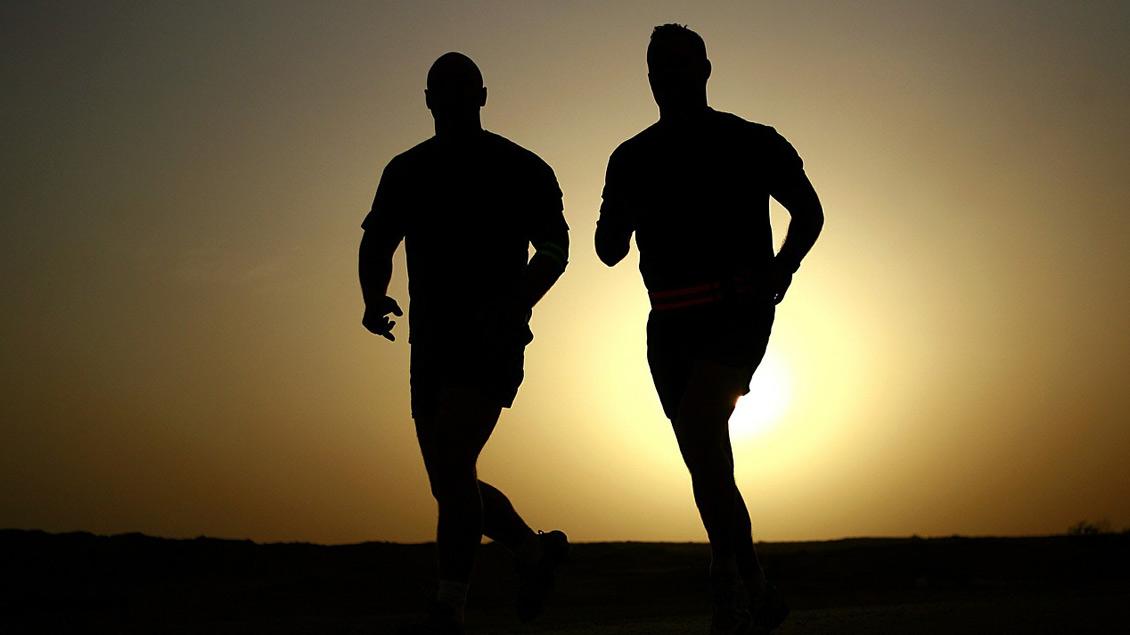 Symbolbild: Zwei joggende Personen in der Dämmerung.