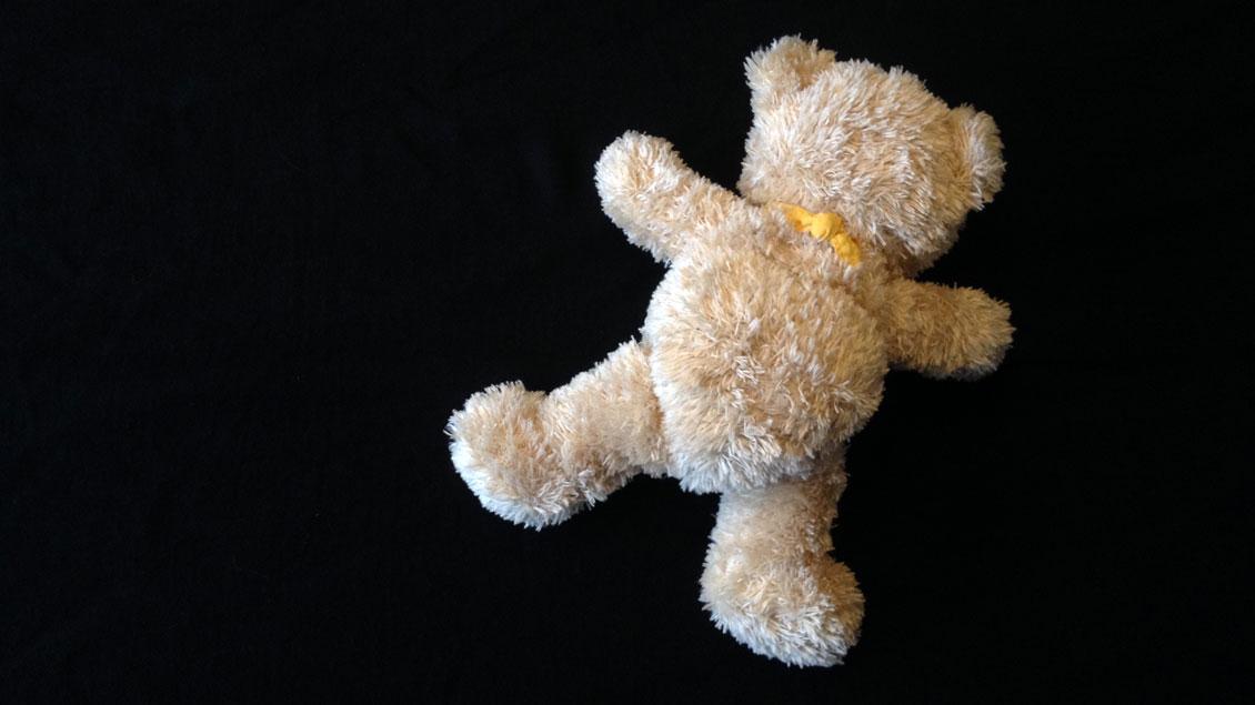 Ein Teddybär liegt auf dem Boden