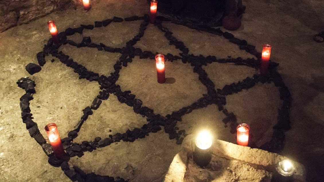 Ein Symbol ritueller Gewalt mit Kerzen