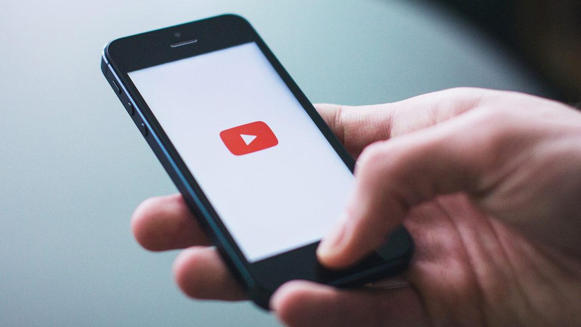Jemand hält ein Smartphone in der Hand, auf dem Youtube geöffnet ist.