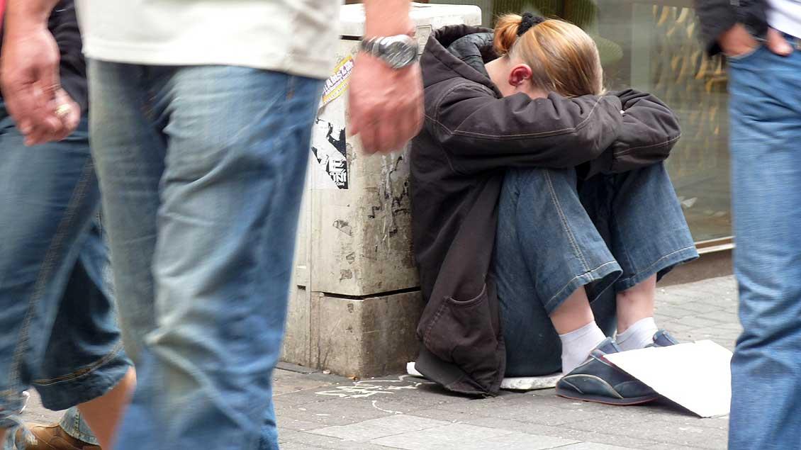 Eine Bettlerin am Straßenrand