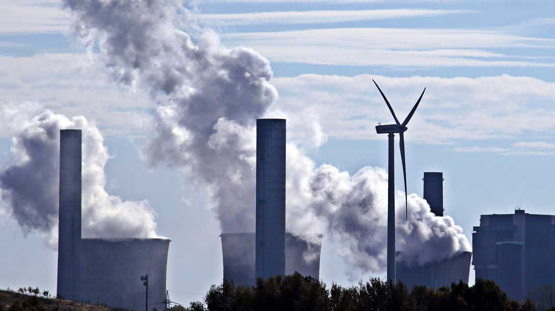Windrad vor Kohlekraftwerk