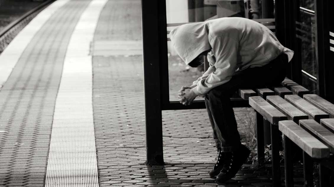 Ein nicht erkennbarer Mensch sitzt an einer Haltestelle