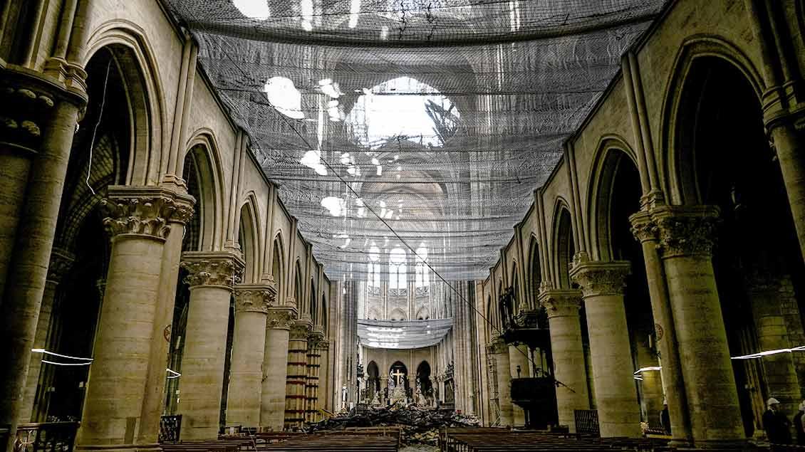 Blick von unten durch ein Sicherheitsnetz durch das zerstörte Dach von Notre Dame