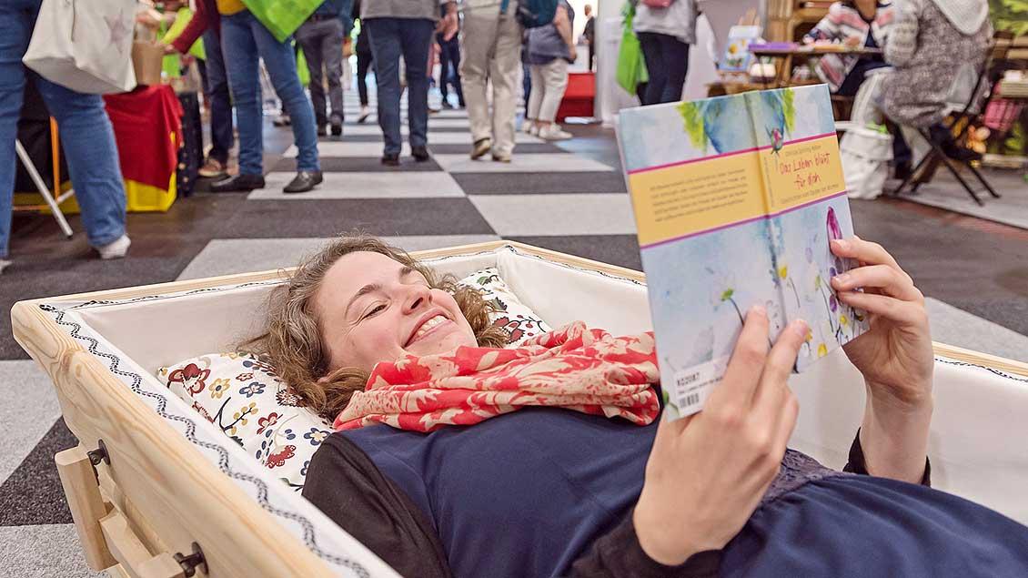 """Eine junge Frau liegt lesend in einem Sarg bei der Ausstellung """"Leben und Tod"""" in Bremen"""