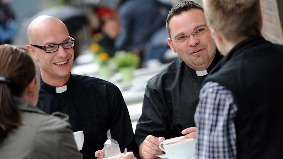 Zwei Priester im Gespräch mit zwei Frauen im Café