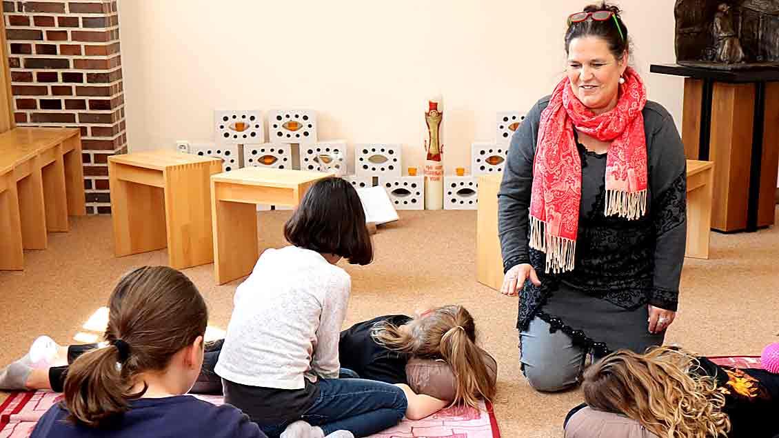 """Yvonne Ahlers kniet im """"Raum der Stille"""" der Paulusschule vor einer Gruppe jüngerer Schülerinnen."""