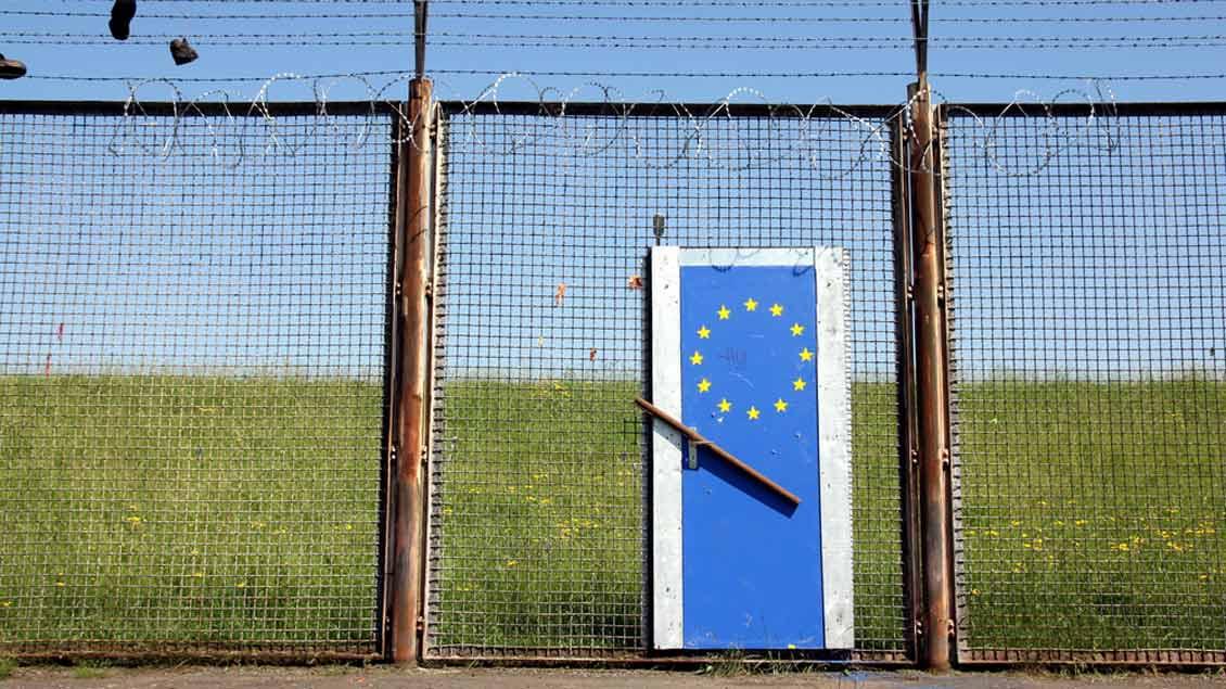 Symbolische Tür mit Europaflagge vor einem Stacheldrahtzaun