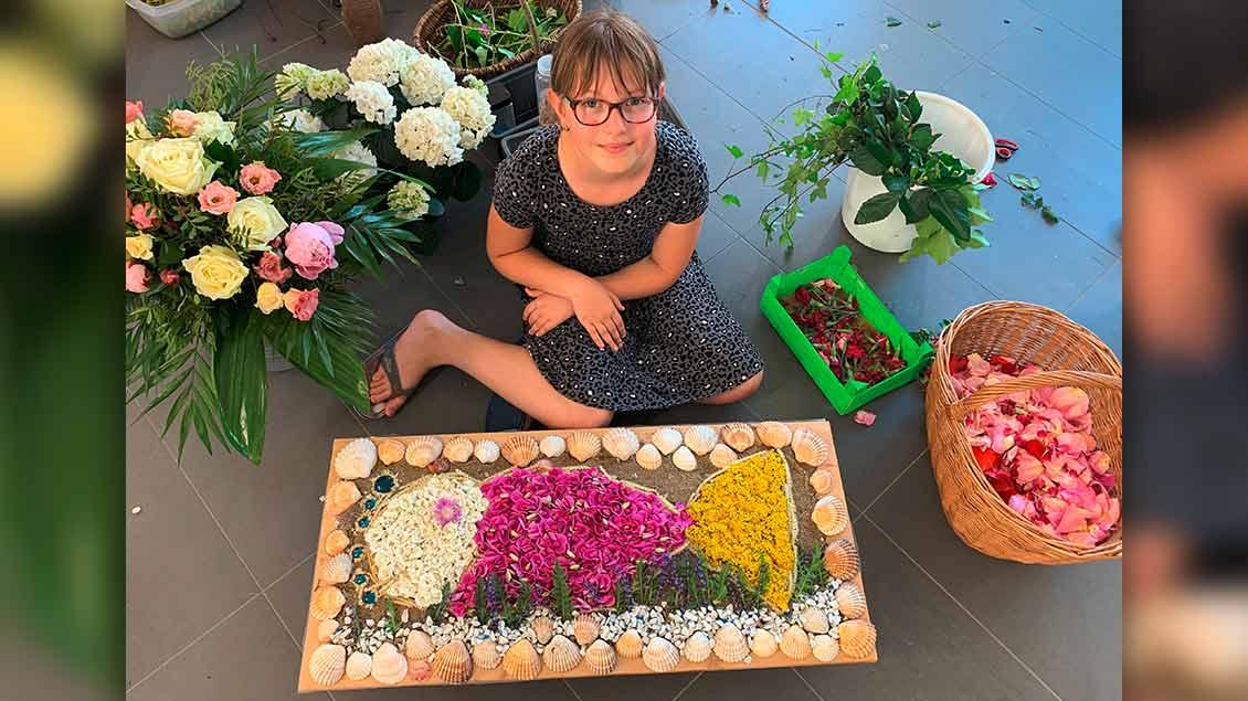 Greta Rakenann (10) hat für die Fronleichnamsprozession in Lengerich ein Fisch-Blumenbild gelegt. | Foto: Marie-Theres Himstedt