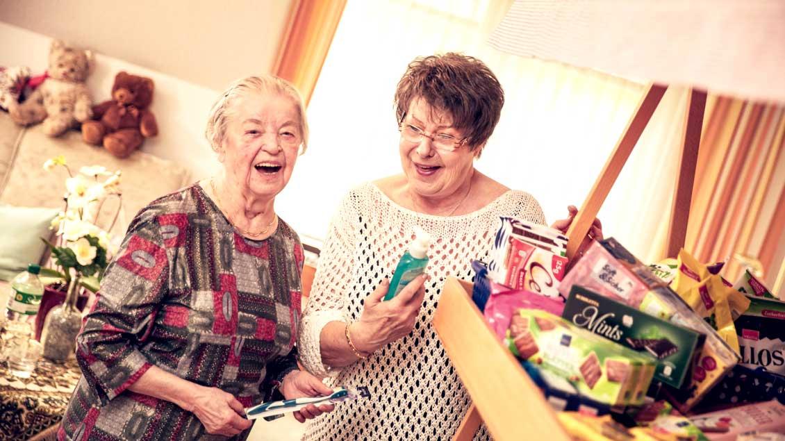 Eine Ehrenamtliche (rechts) versorgt eine Seniorin im Caritas-Altenheim.
