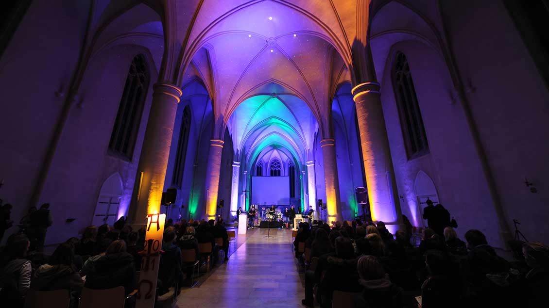 Die Jugendkirche Effata in Münster ist während eines Gottesdienstes farbig ausgeleuchtet.