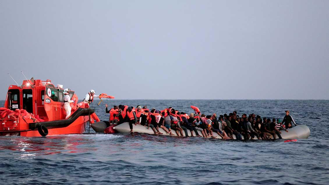Auf dem Meer schwimmt ein sehr volles Schlauchboot. Daneben ein Rettungsboot. Helfer verteilen Schwimmwesten an die Menschen auf dem Schlauchboot.