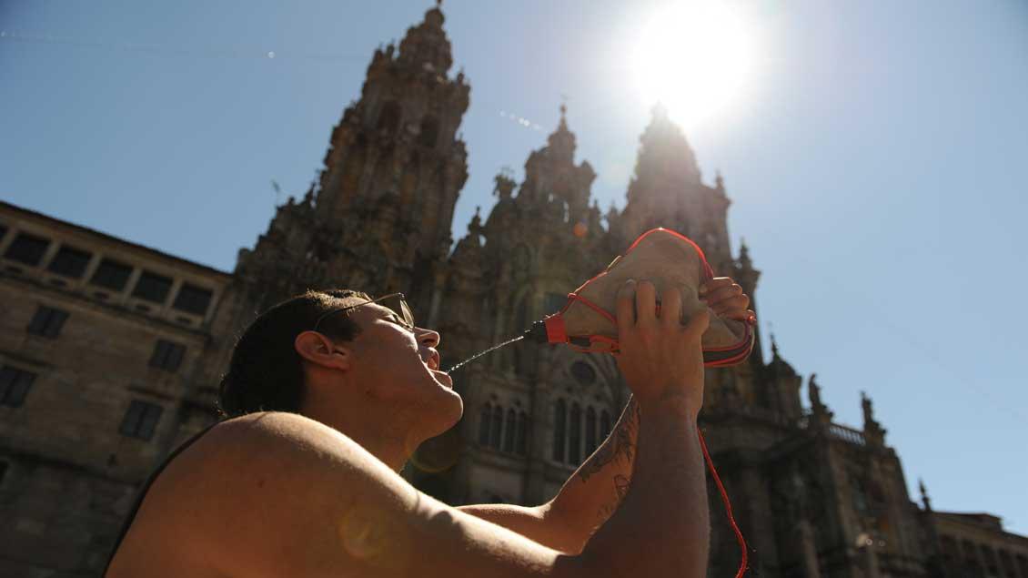 Pilger in Santiago de Compostela trinkt in der Sonne Wasser