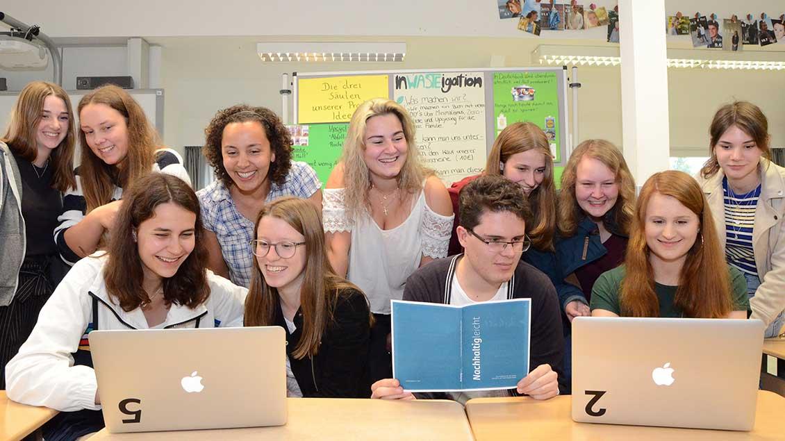 Schülerinnen und Schüler vor Laptops.