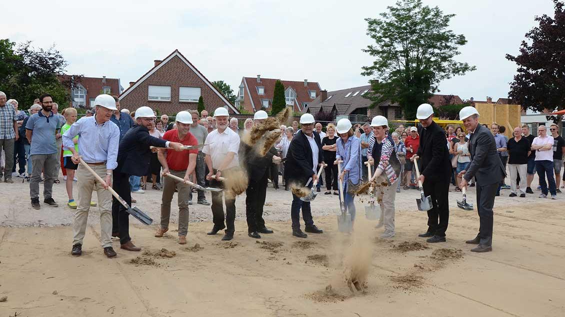 Zehn wichtige Männer und Frauen schmeißen mit Spaten Sand durch die Gegend.
