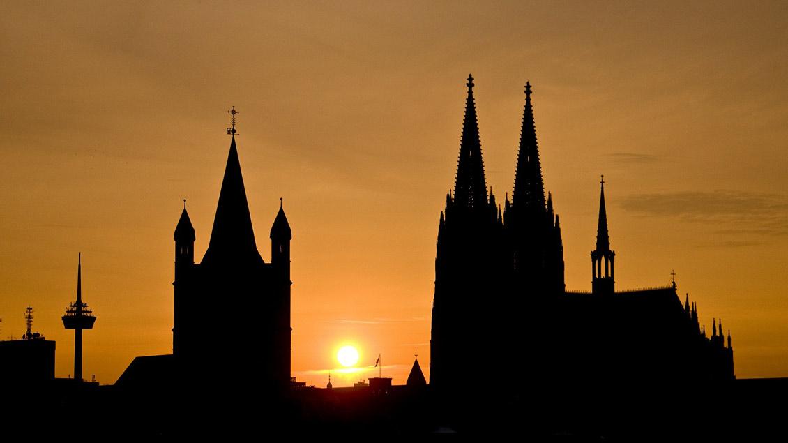 Groß St. Martin und Kölner Dom im Abendlicht.