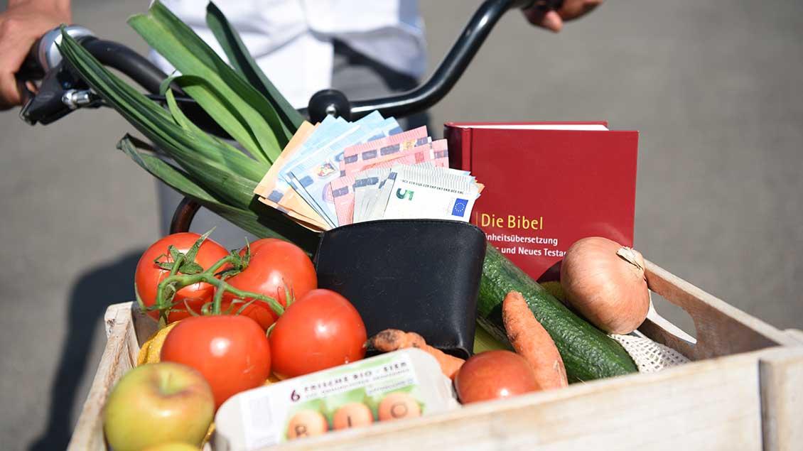 Korb mit Gemüse, Geld, Eiern und Bibel auf einem Fahrrad.
