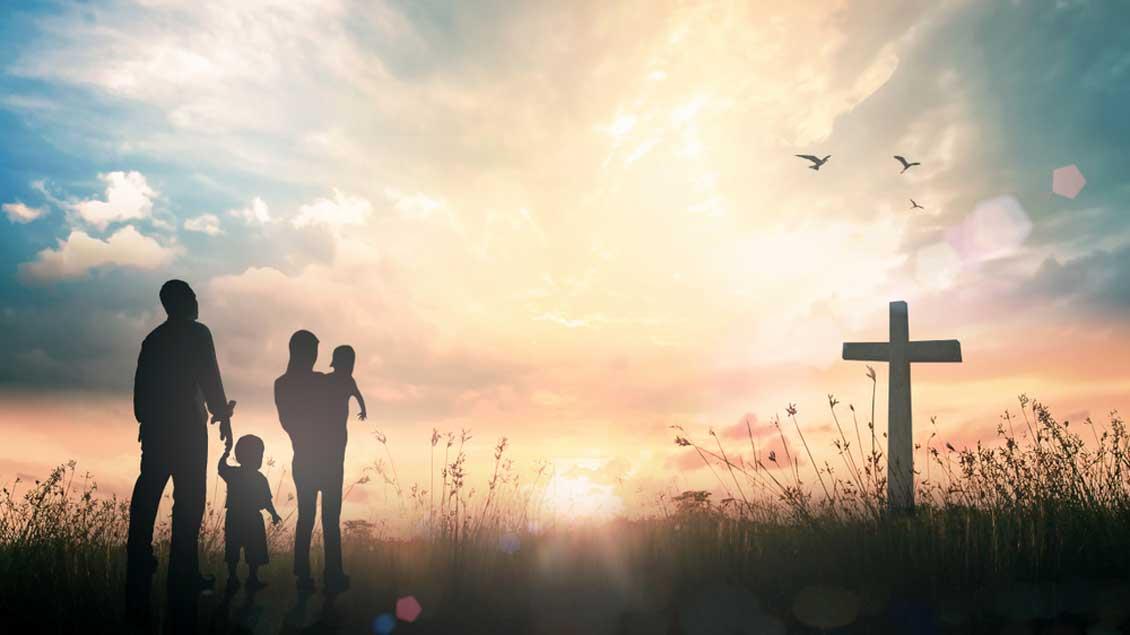 Eine Familie neben einem Kreuz im Sonnenuntergang