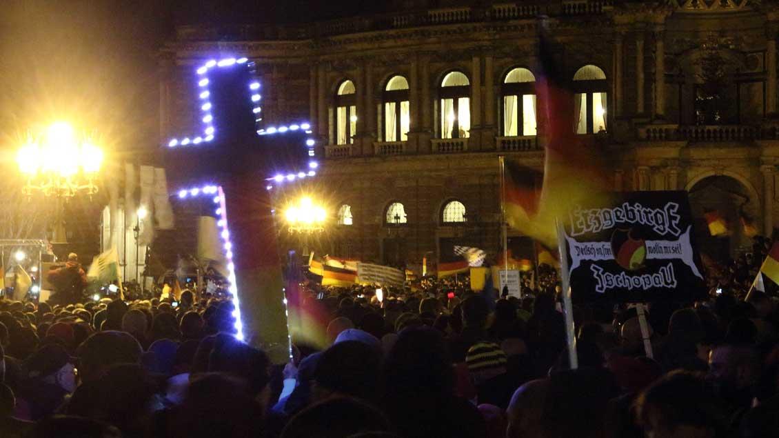 Pegida-Demonstration mit Kreuz und Deutschlandfahne in Dresden