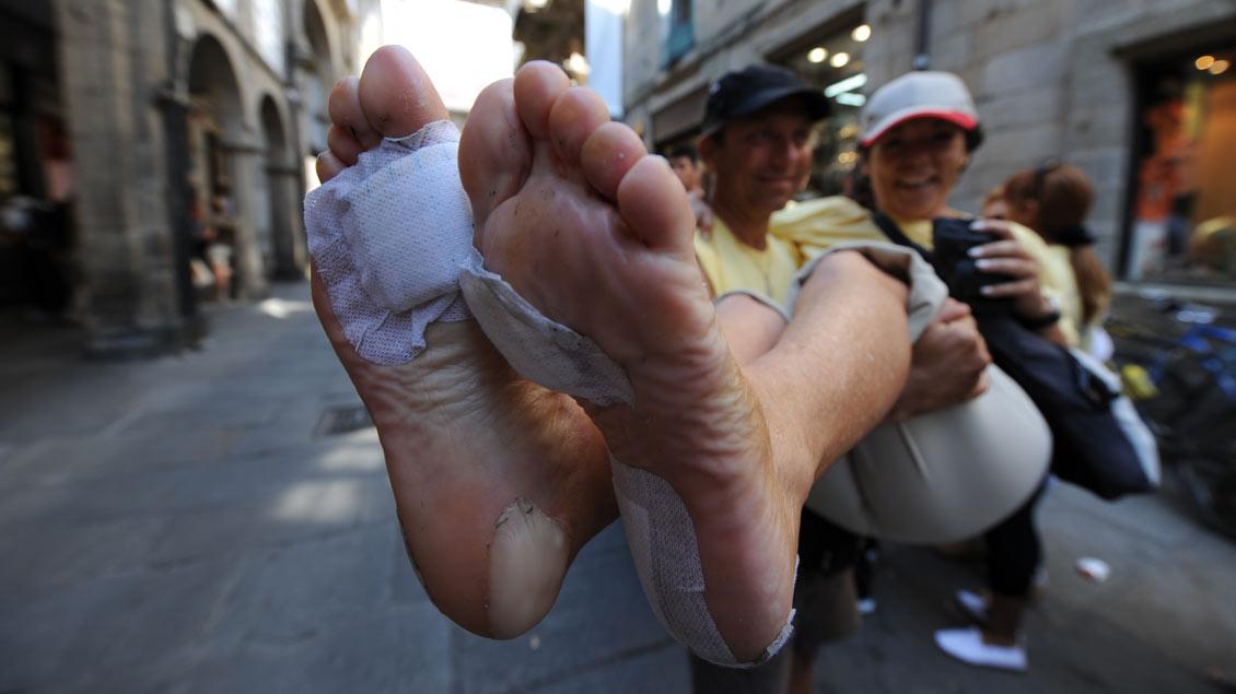 Ein Mann hebt eine Frau hoch die ihre Fußblasen zeigt.