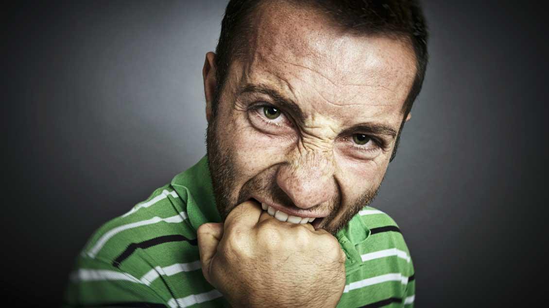 Ein Mann beißt sich in die eigenen Faust. Foto: Alexandru Logel (Shutterstock)