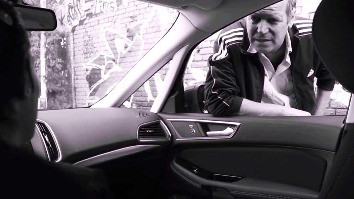 Prostituierter beugt sich durch das geöffnete Fenster ins Auto der Freierin.