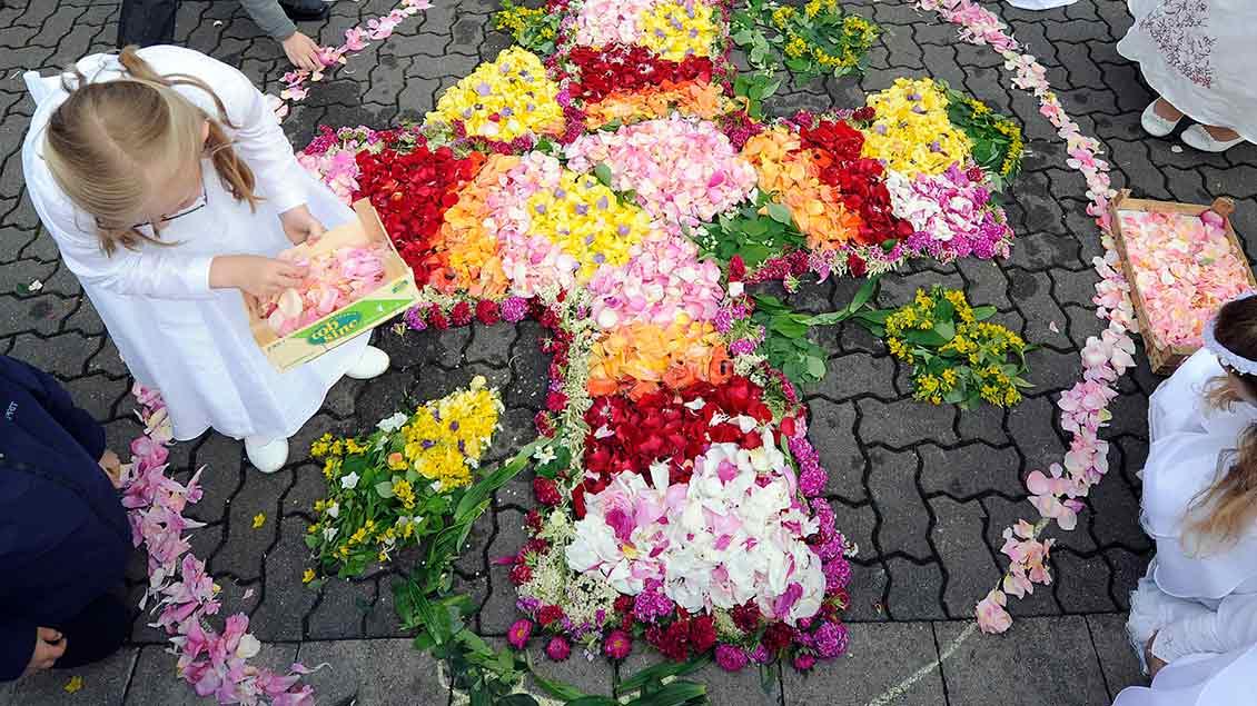 Kommunionkinder legen Blumen zu einem Kreuz. Archiv-Foto: Dirk Bauer