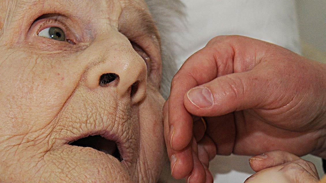 Eine Hand streichelt die Wange eine sehr alten Frau.