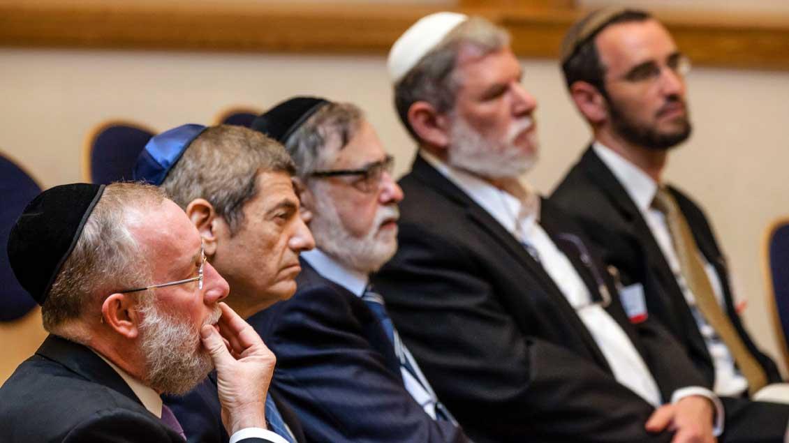 Jüdische Männer mit Kippa hören zu