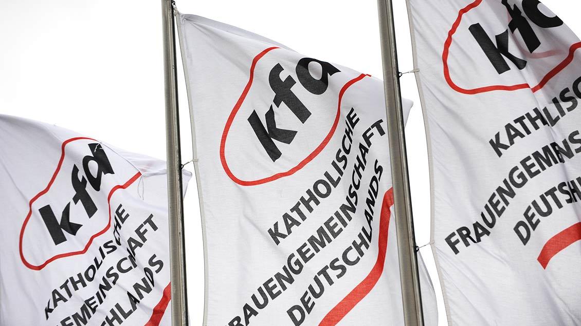 Fahnen mit dem kfd-Logo wehen im Wind.
