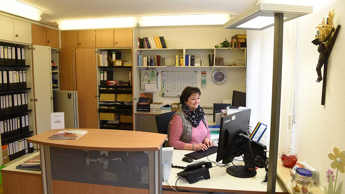 Eine Pfarrsekretärin arbeitet in ihrem Büro.
