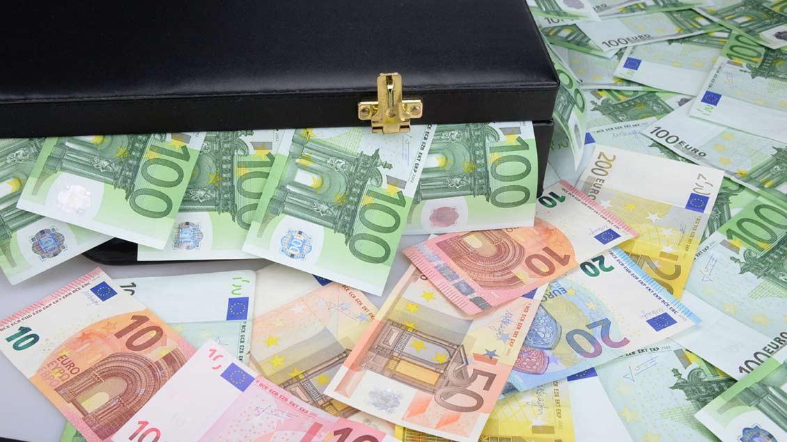Aus einem schwarzen Geldkoffer kommen viele Euro-Scheine. Foto: fotoART by Thommy Weiss (pixelio.de)