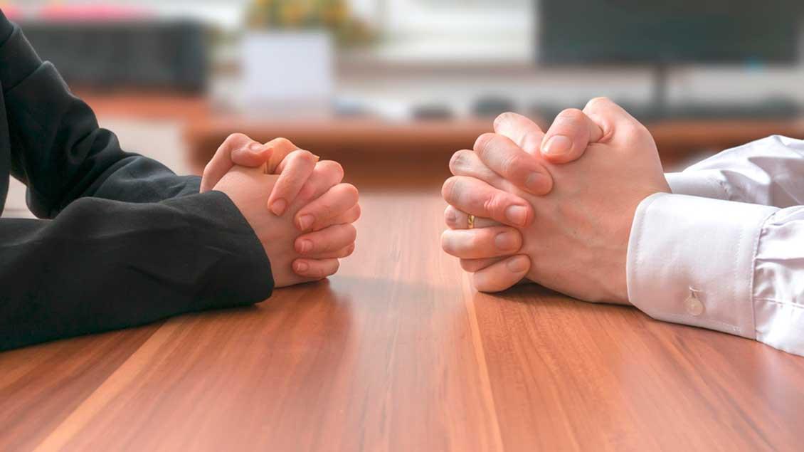 Zwei Menschen sitzen am Verhandlungstisch einander gegenüber. Foto: vchal (Shutterstock)