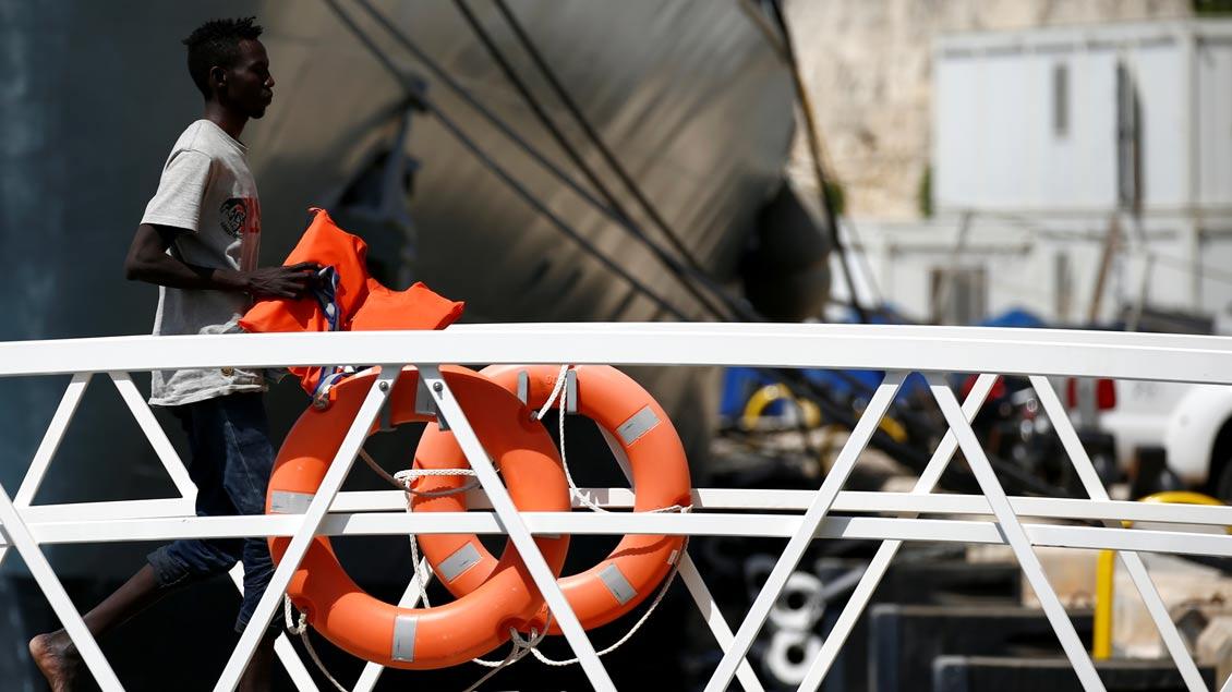Ein farbiger Mann verlässt mit einer Rettungsweste ein maltesisches Militärboot.
