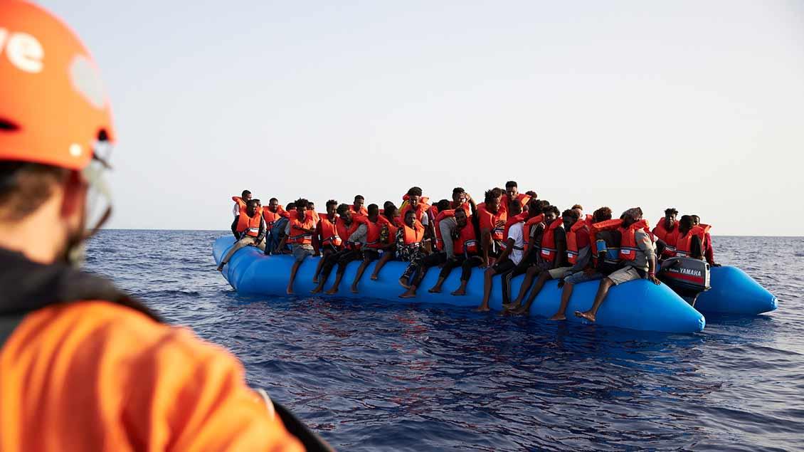 Migranten auf einem Schlauchboot, im Vordergrund ein Mitarbeiter der Organisation Sea-Eye.