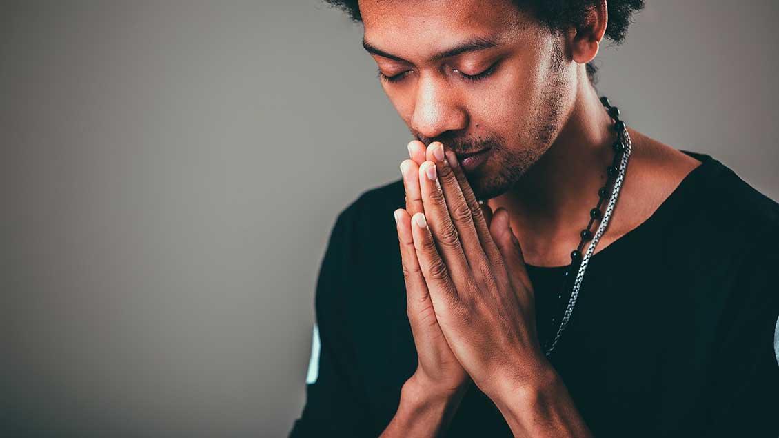 Ein Mann legt die Hände im Gebet aneinander