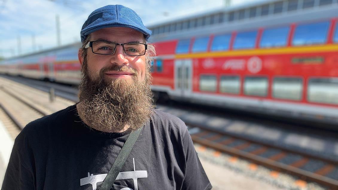 Hanno Rother vor einem Regionalzug der Deutschen Bahn.