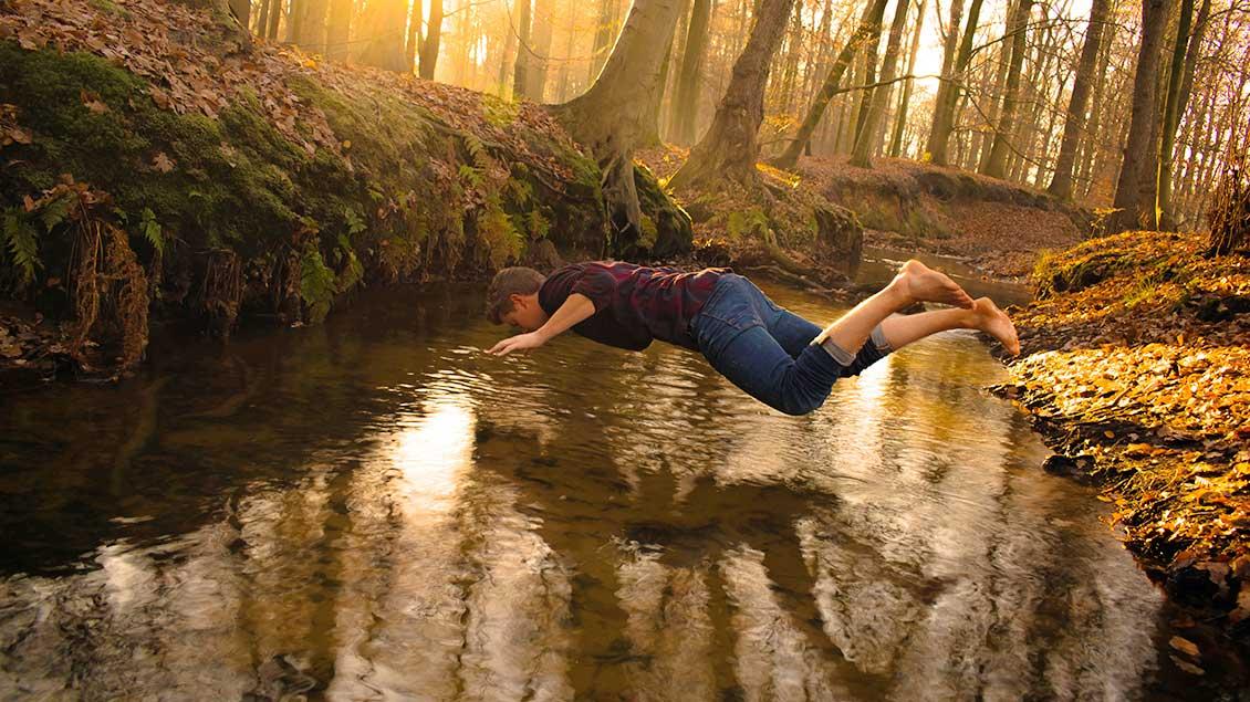 Ein Mann liegt quer über einem Wasserlauf