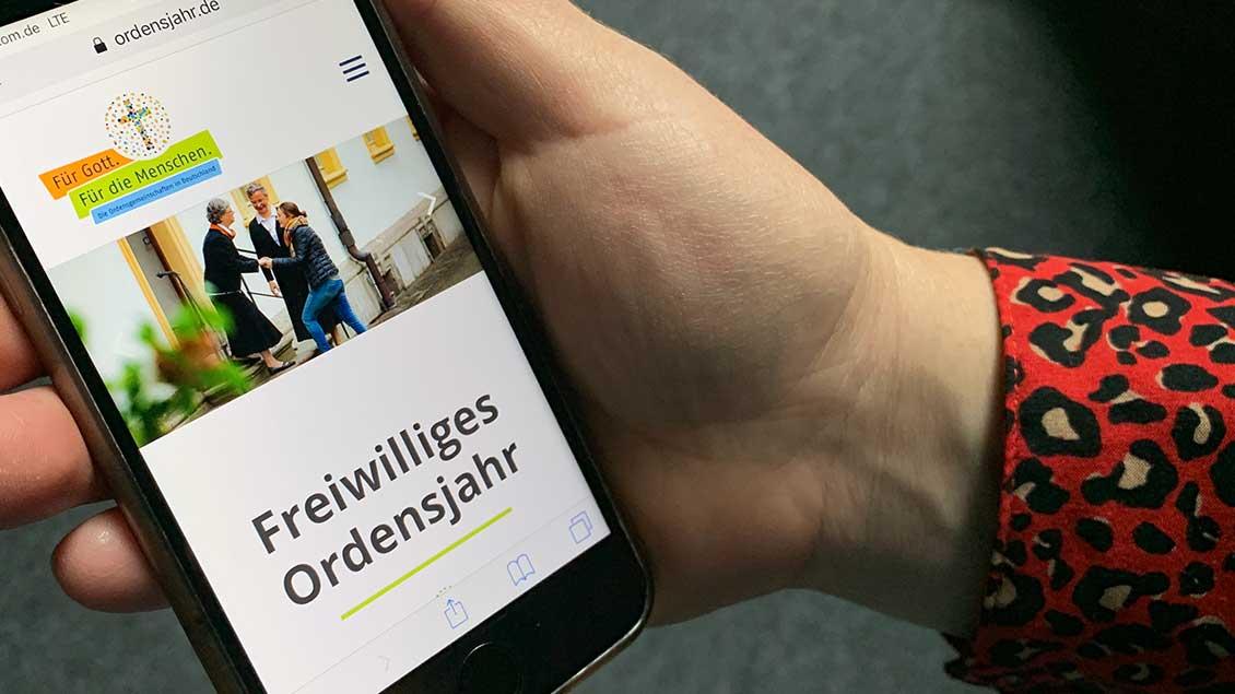 Hand hält Handy mit der Internetseite www.ordensjahr.de