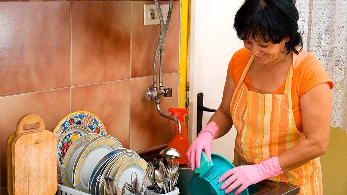 Eine Frau mit Schürze macht den Abwasch in einer Küche.