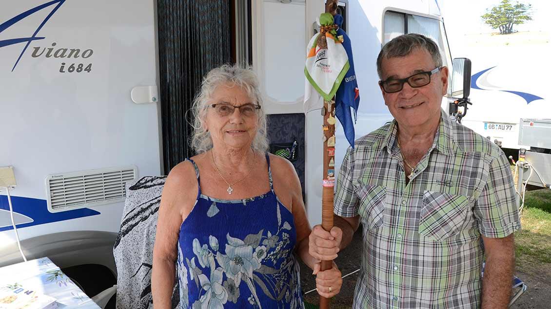 Elke Cherdron und Peter Risler halten gemeinsam einen großen, hölzernen Pilgerstab, der mit zahlreichen Buttons und Tüchern geschmückt ist.