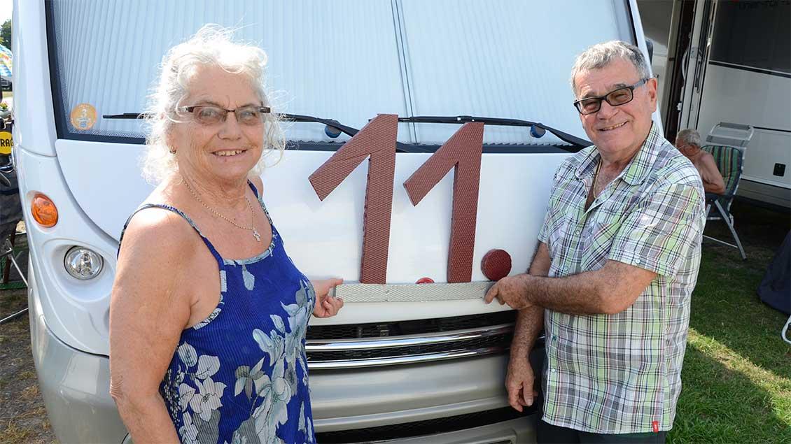 Elke Cherdron und Peter Risler halten eine selbstgebastelte 11 vor ihr Wohnmobil.