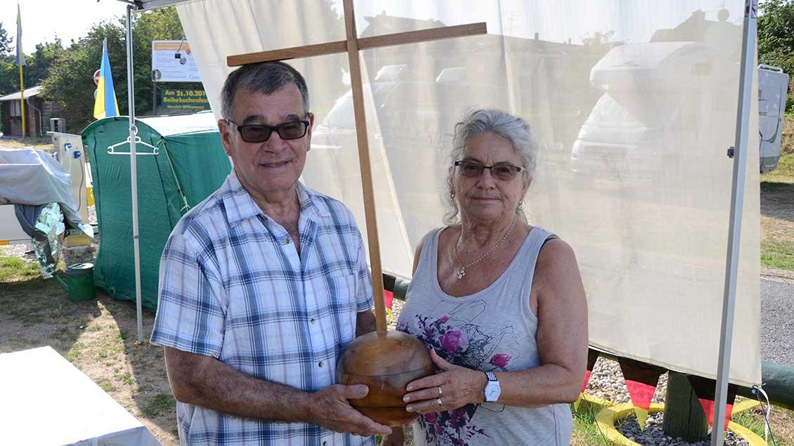 Peter Risler und Elke Cherdron präsentieren das selbst gebastelte Holzkreuz.